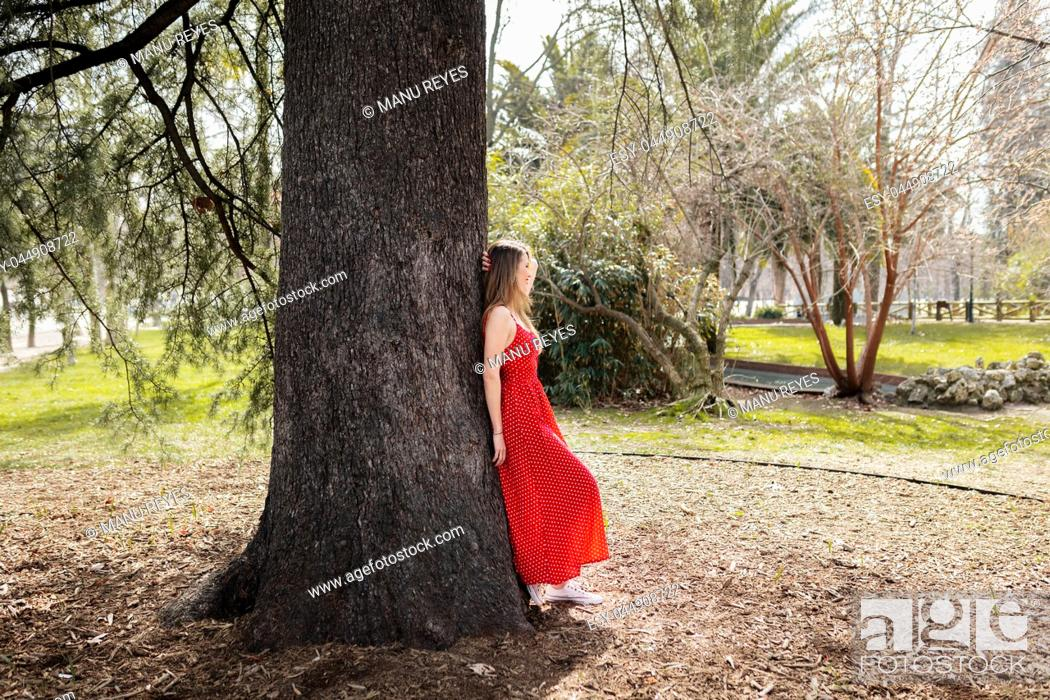 Imagen: Young smiling blond woman with red dress leaning against a tree.