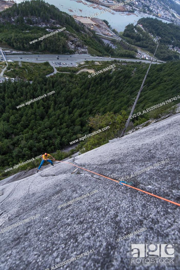 Stock Photo: Man rock climbing and swinging around with exposed view Squamish Chief.