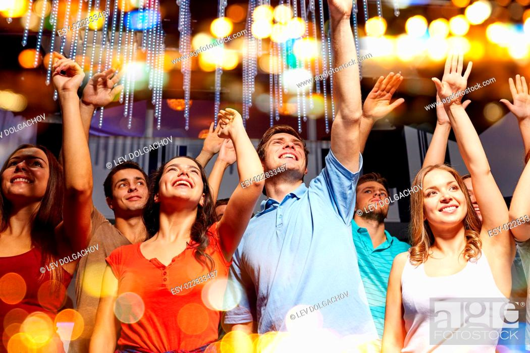 Stock Photo: party, holidays, celebration, nightlife and people concept - group of smiling friends waving hands at concert in club.