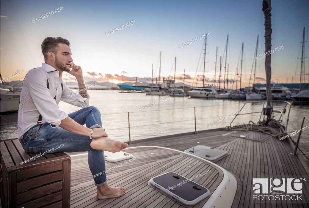 Imagen: Young man using smartphone on yacht, Cagliari, Sardinia, Italy.