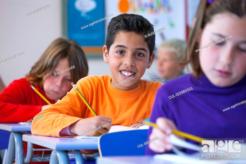 Stock Photo: Portrait of boy in classroom, sitting at desk, doing classwork.
