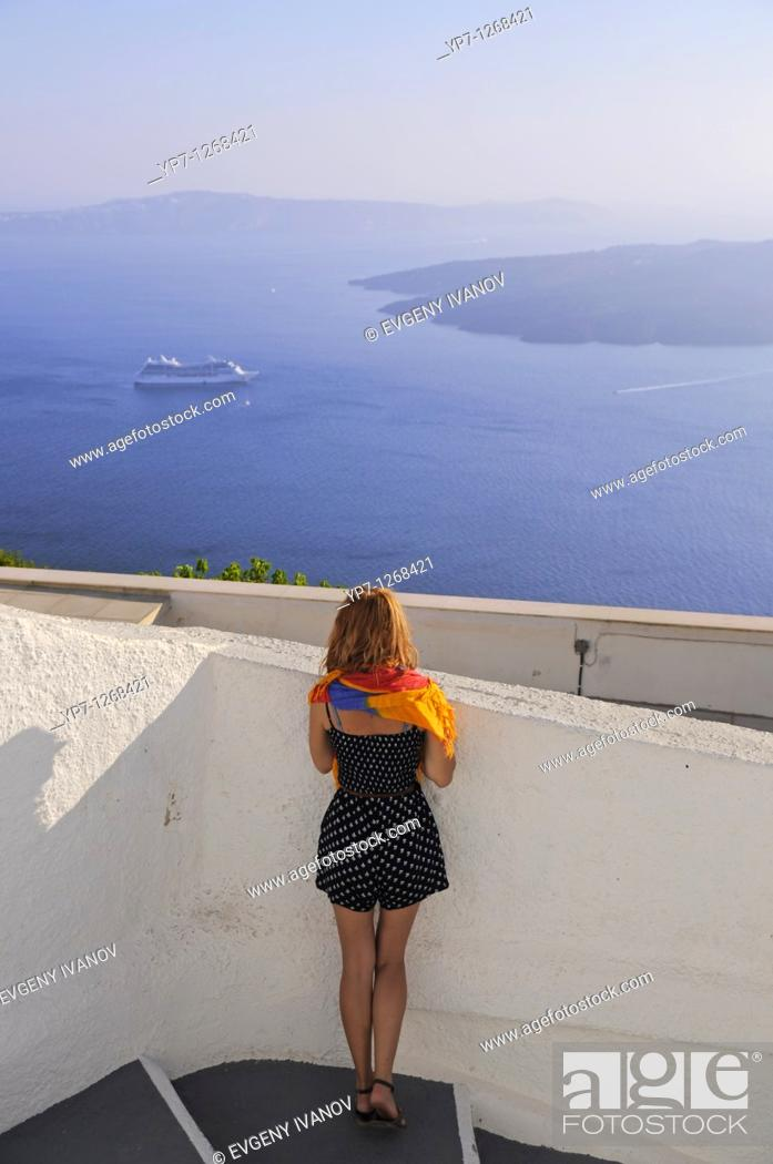 Stock Photo: Girl in Santorini looking at the ferry leaving the port and volcano caldera.