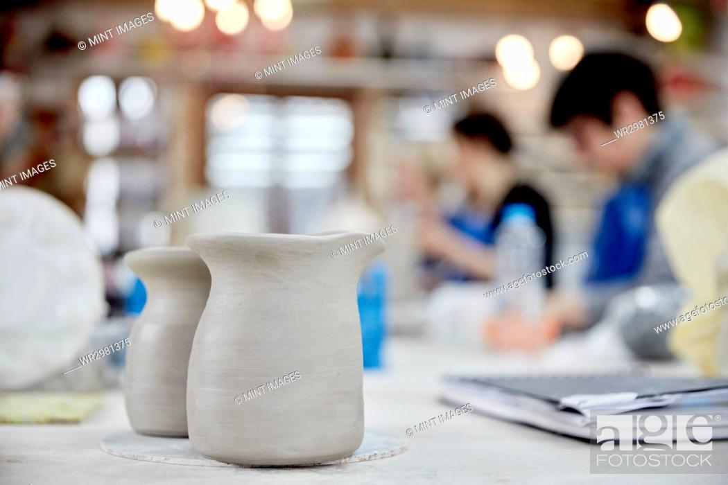 Photo de stock: Two clay jugs in the foreground. A ceramics class taking place, people seated at a workbench in a pottery studio.