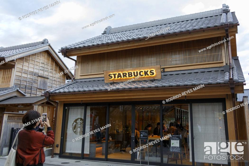 Stock Photo: December 5, 2018, Saitama, Japan - A woman takes a picture of a Starbucks coffee shop in Kawagoe. The branch opened last March is located near to the Toki no.