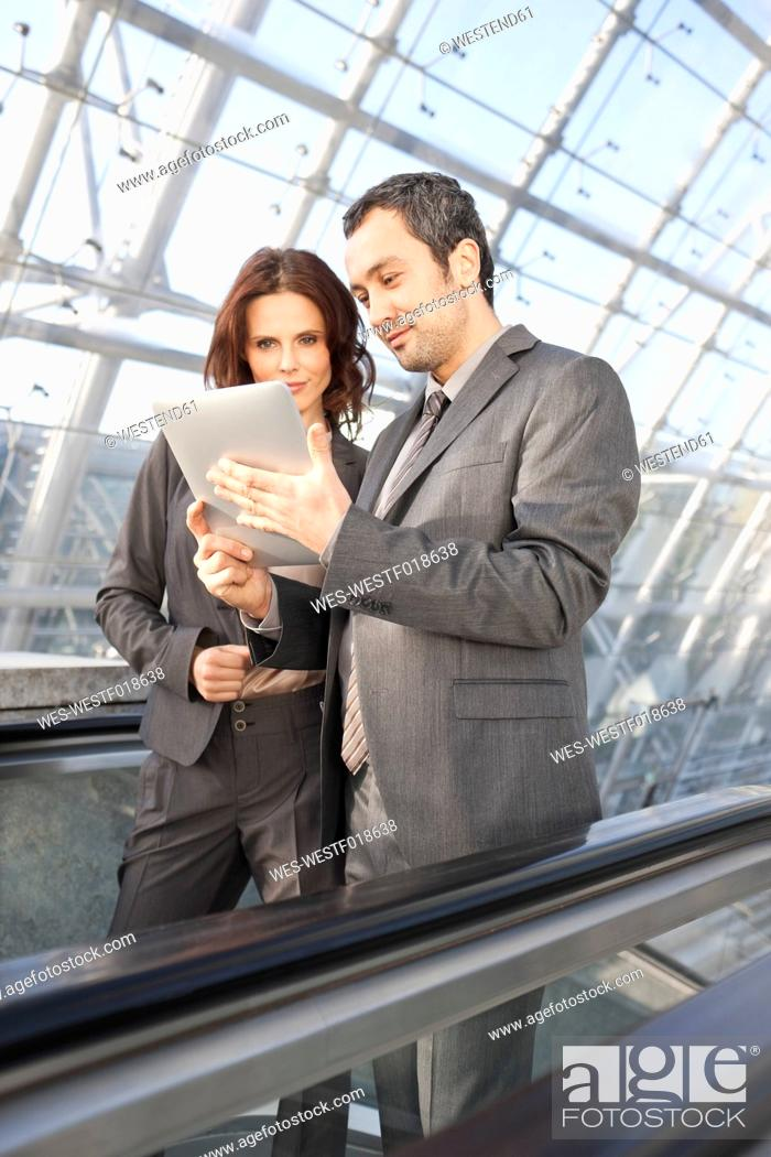 Stock Photo: Germany, Leipzig, Business people using digital tablet on escalator.