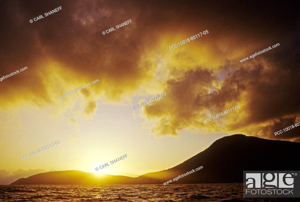 Stock Photo: Dramatic sunset sky as sun sinks behind mountains and ocean.