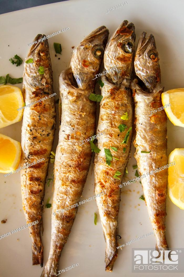 Stock Photo: A traditional Greek food dish with small Hakes and lemons. Peloponnese, Greece.