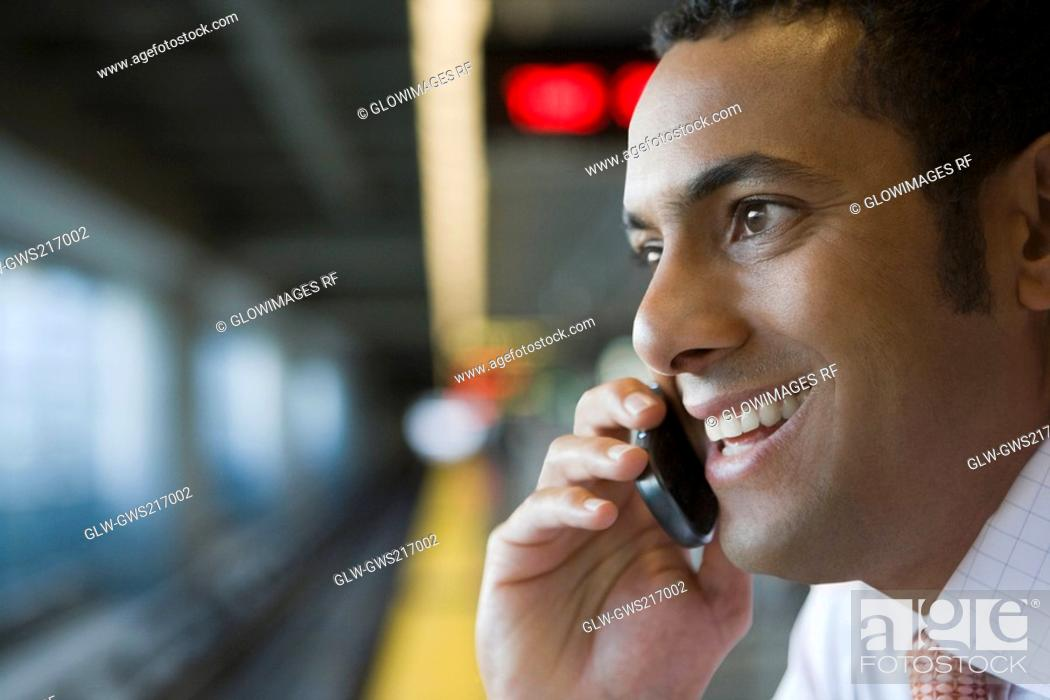 Stock Photo: Close-up of a businessman talking on a mobile phone at a subway station.