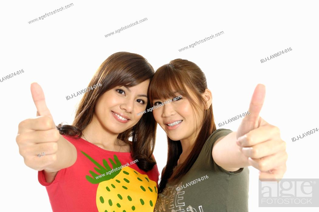 Stock Photo: Female university students showing thumbs up sign.