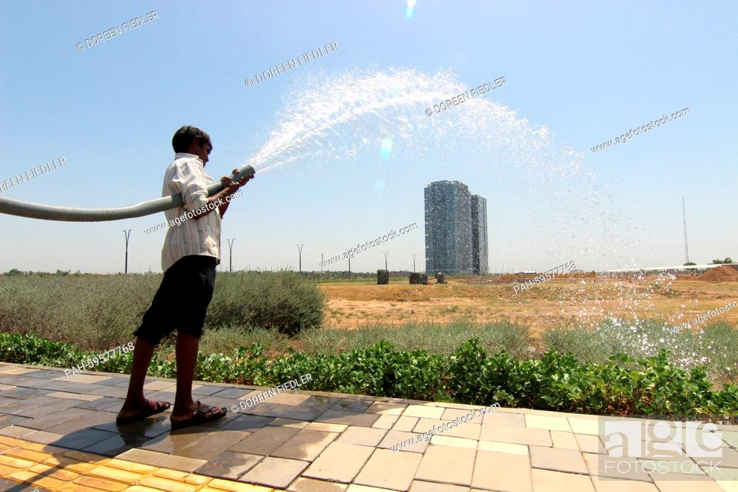 Stock Photo: A gardener waters the plants in the satellite town GIFT City (Gujarat International Finance Tec-City) in Gandhinagar, India, 16 May 2015.