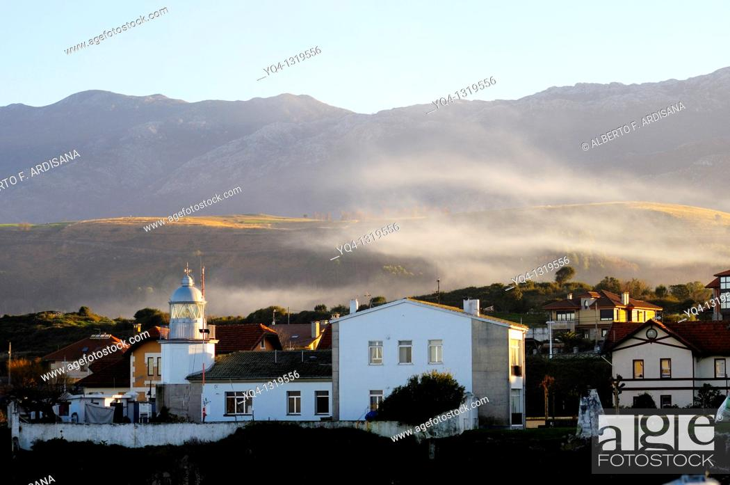 Stock Photo: LLanes Lighthouse in a winter day, in the background the Sierra del Cuera, Llanes, Asturias, Spain.
