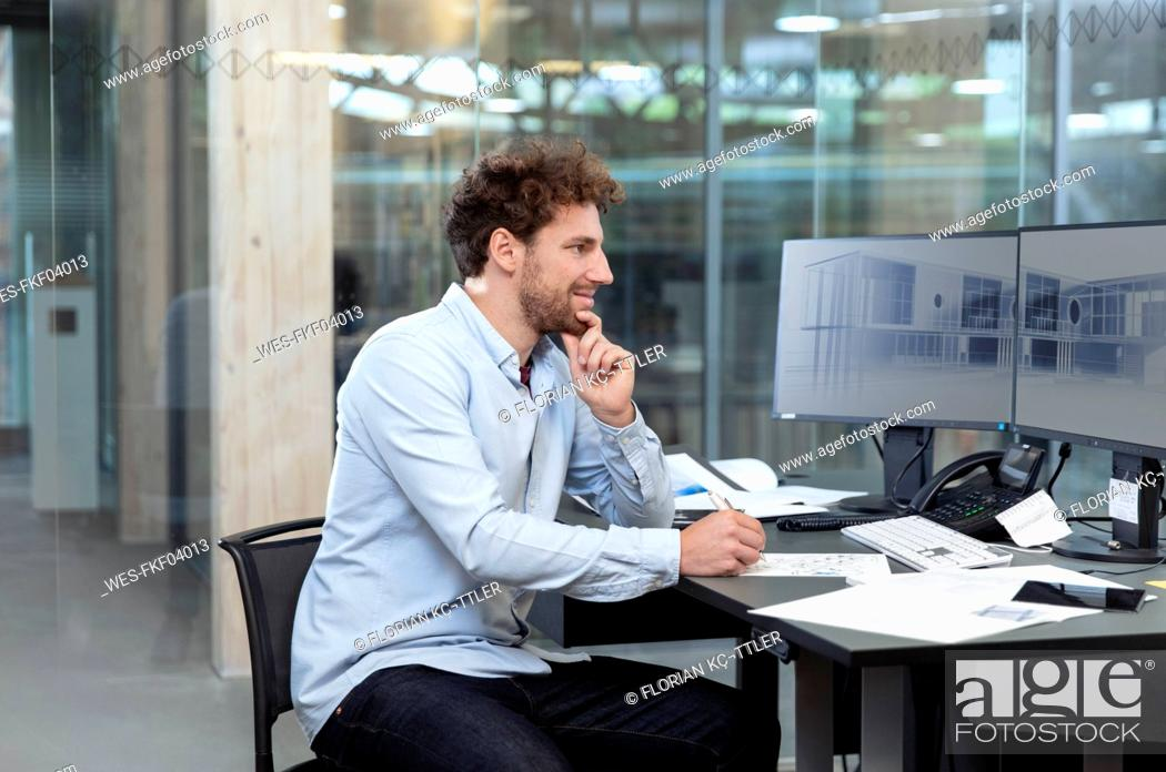 Stock Photo: Thoughtful male entrepreneur writing while sitting at computer desk in factory.