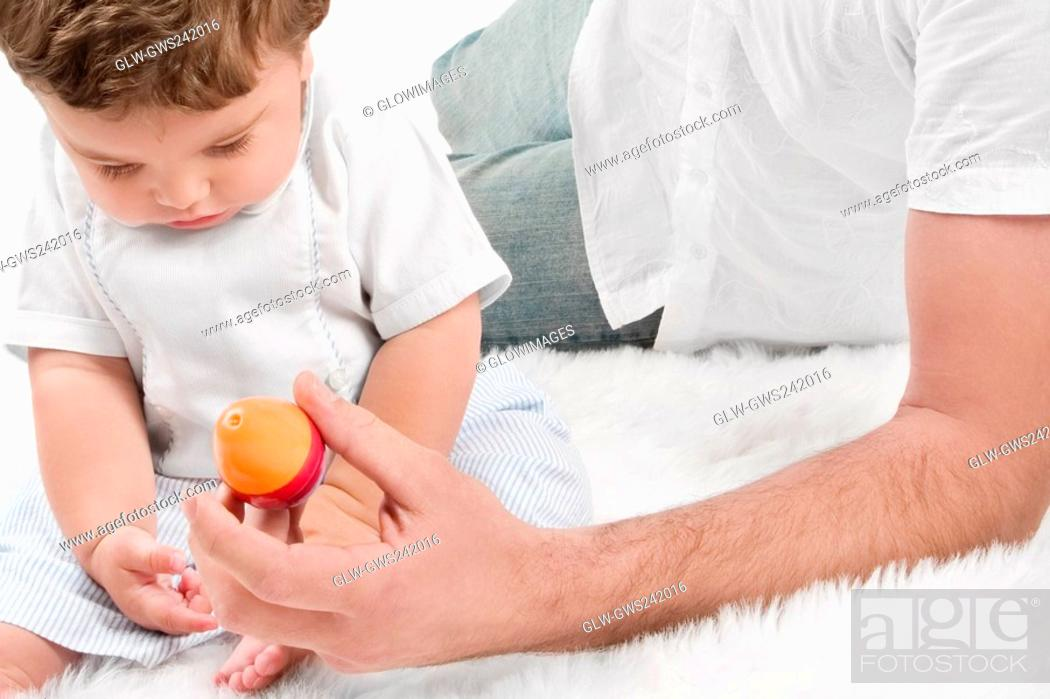 Stock Photo: Mid section view of a young man playing with his son.