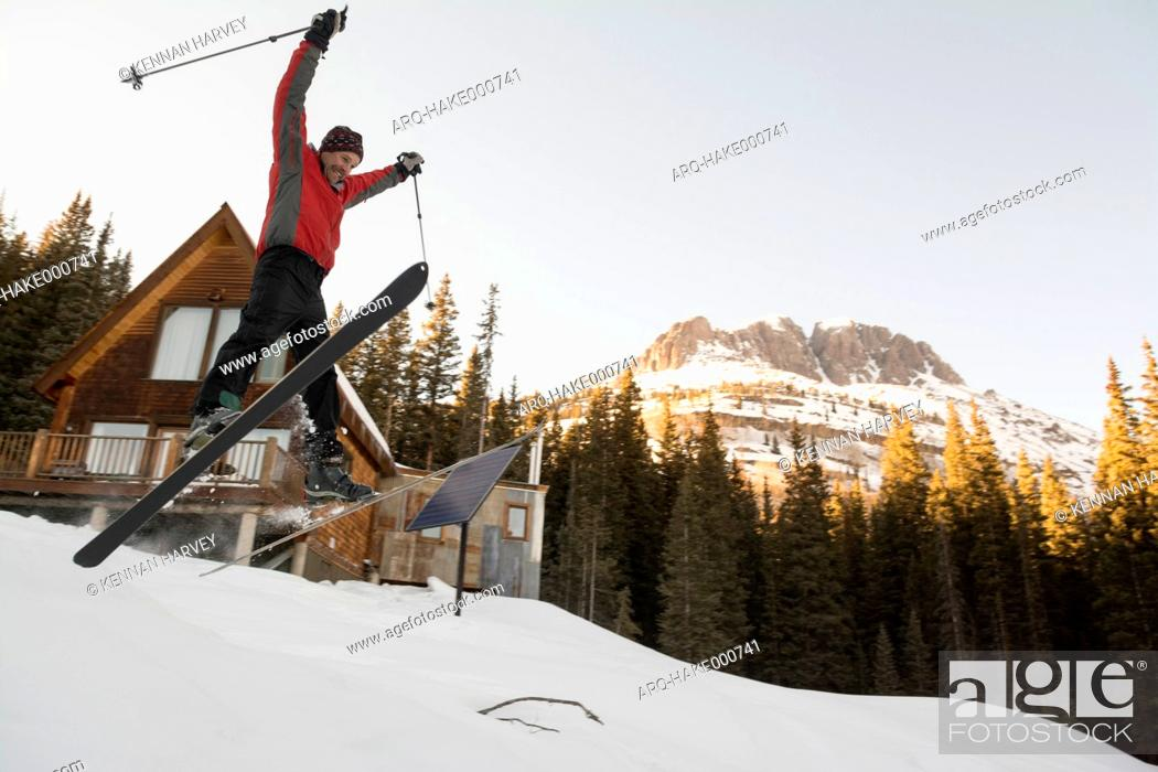 Imagen: A man jumping on his skis in front of backcountry hut.