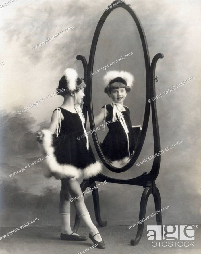 Stock Photo: San Francisco, California: c. 1905.A young girl admires her outfit in a mirror.