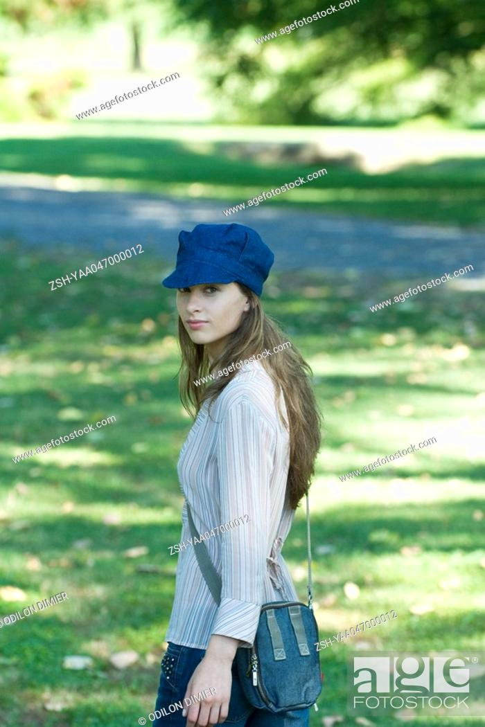 Stock Photo: Young woman walking through park, wearing cap, looking over shoulder at camera.
