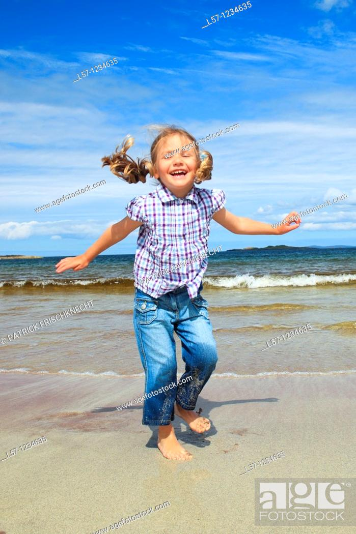 Stock Photo: girl playing on sandy beach, Sutherland, Scotland.