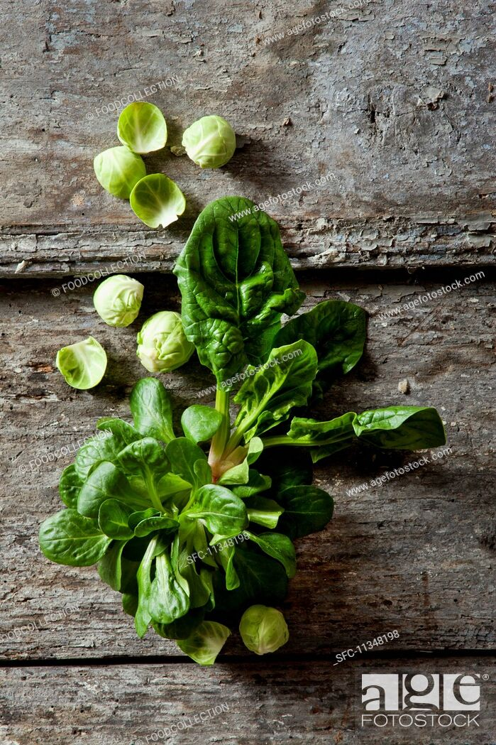 Stock Photo: Organic spinach, lamb's lettuce and Brussels sprouts on a wooden surface.