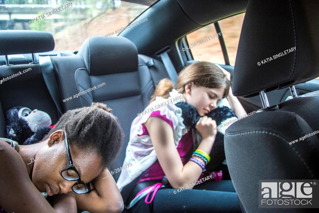Stock Photo: 2 girls, one caucasian preteen and one african american teen in the car sleeping and resting with stuff animals and earphones on.