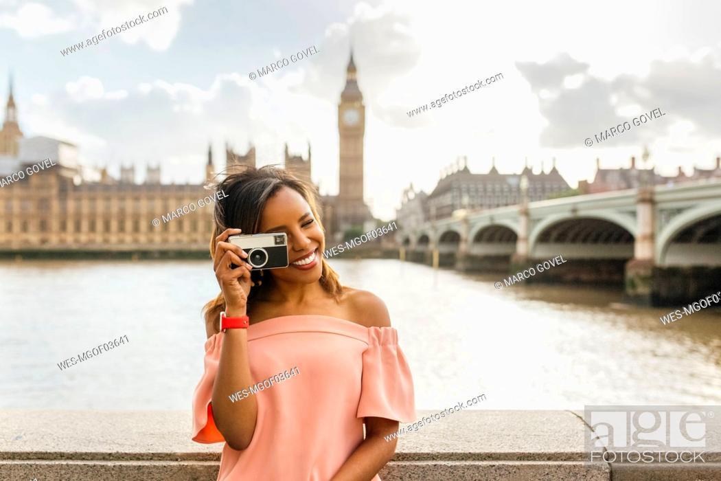 Stock Photo: UK, London, beautiful woman taking a picture near Westminster Bridge.
