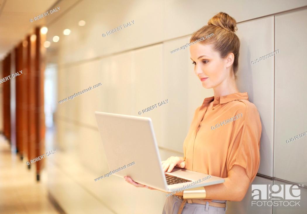 Stock Photo: Businesswoman using laptop in corridor.