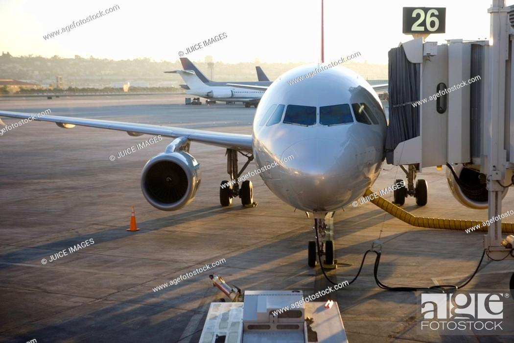 Stock Photo: Stationary commercial aircraft at airport boarding gate, front view.