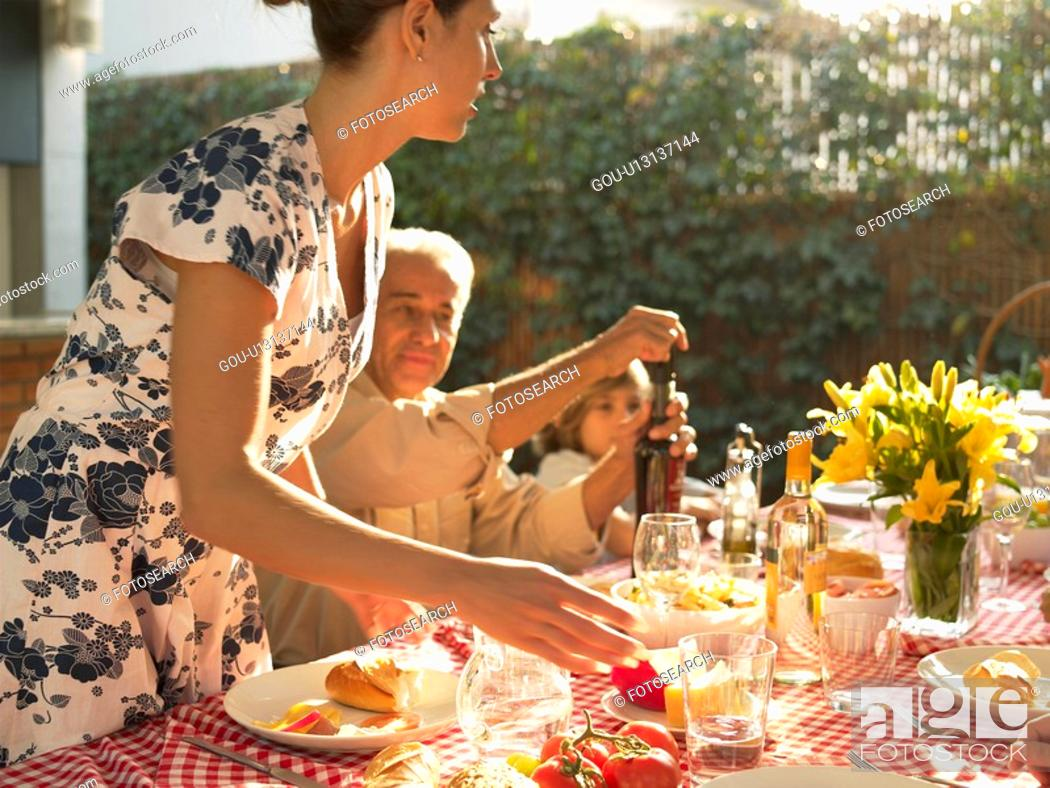Photo de stock: Family at dinner table in garden.