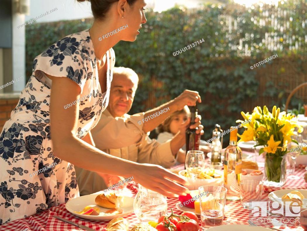 Imagen: Family at dinner table in garden.