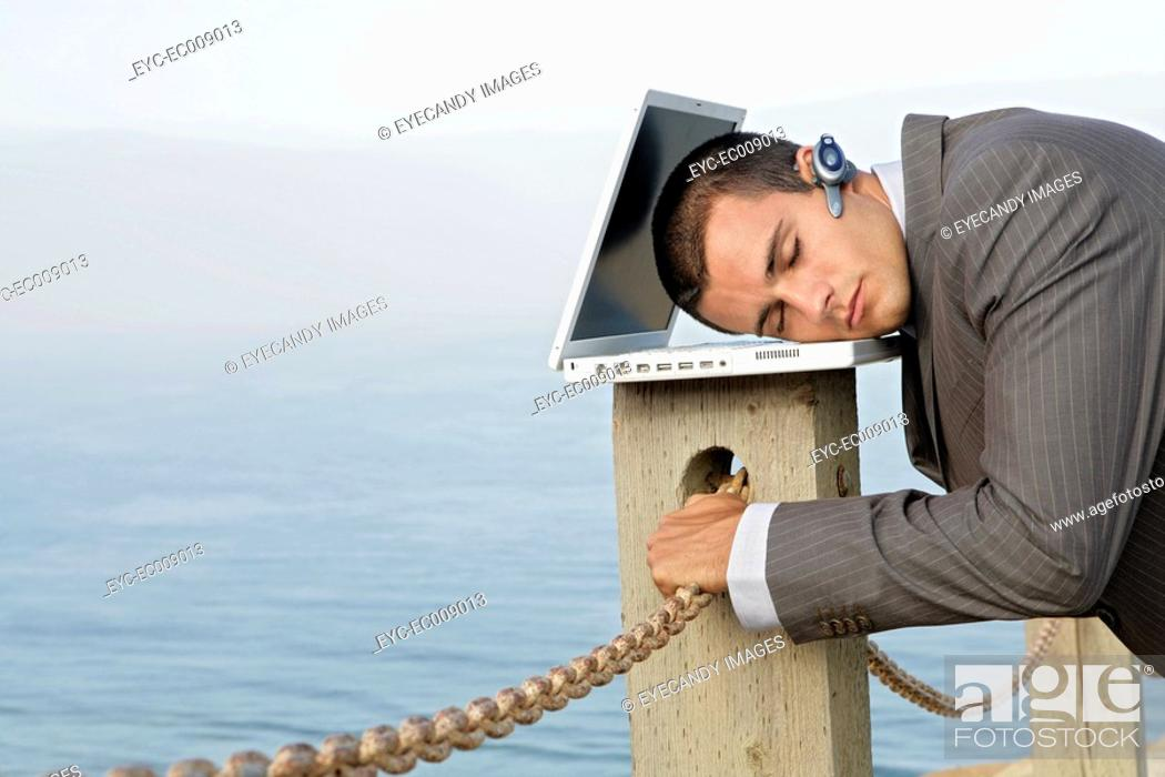 Stock Photo: View of a man sleeping on a laptop.