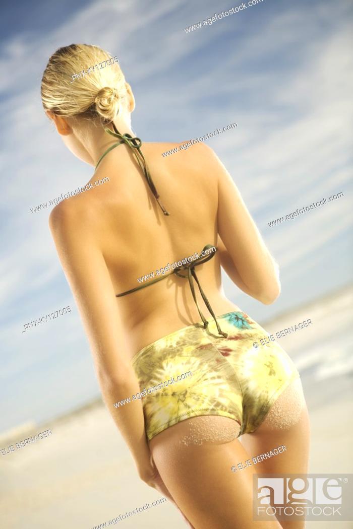 Stock Photo: Young woman in bikini standing on beach, rear view.