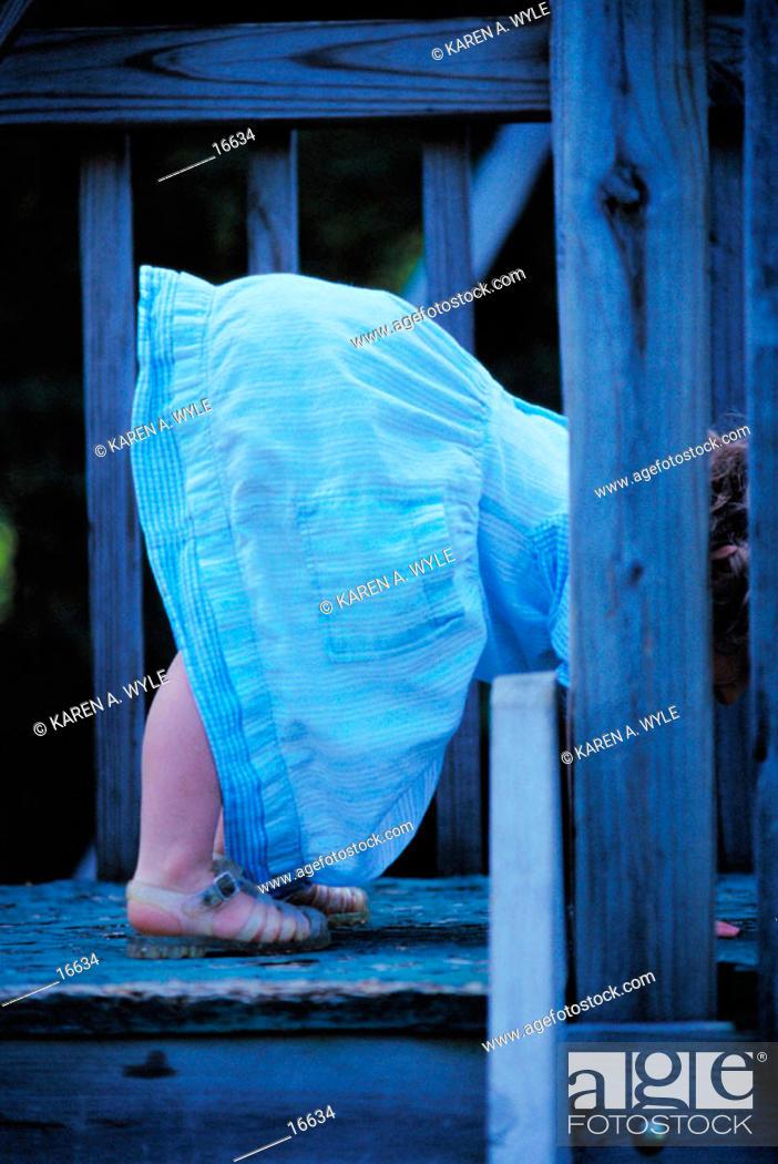 Imagen: Little girl in blue denim dress bending over.
