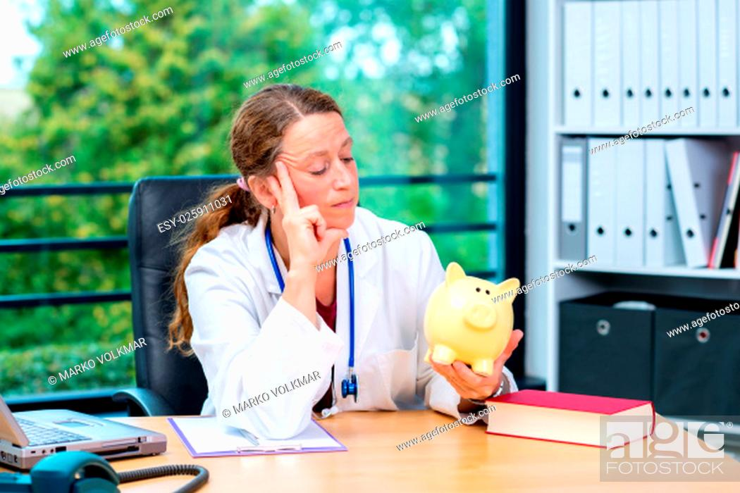 Stock Photo: young female doctor in her office with a piggy bank.