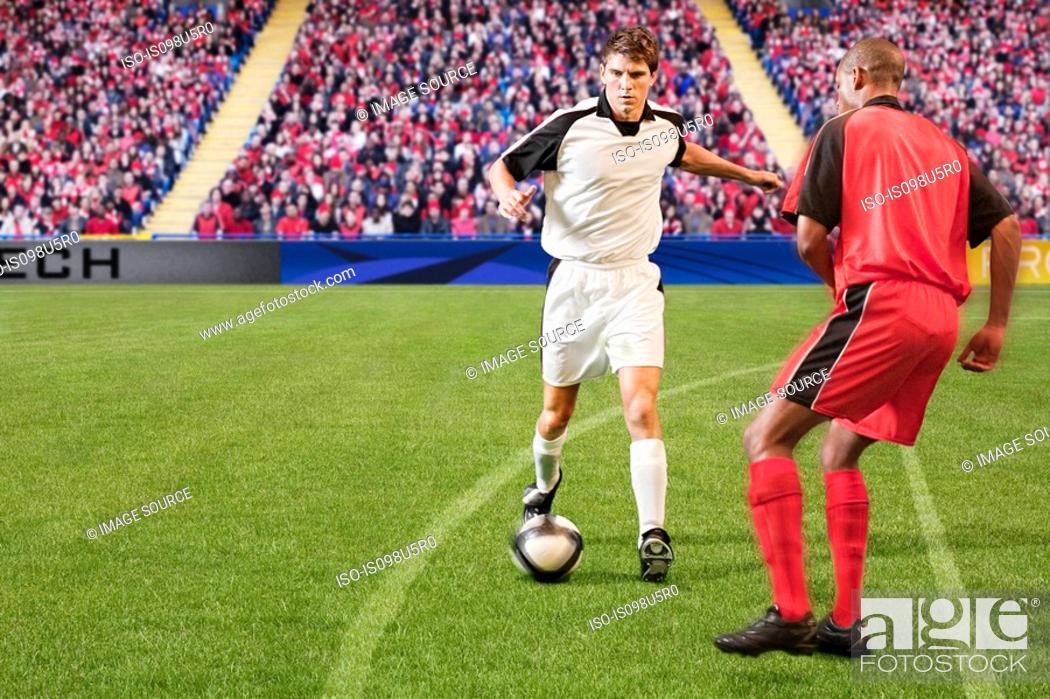 Stock Photo: Football players kicking the ball.