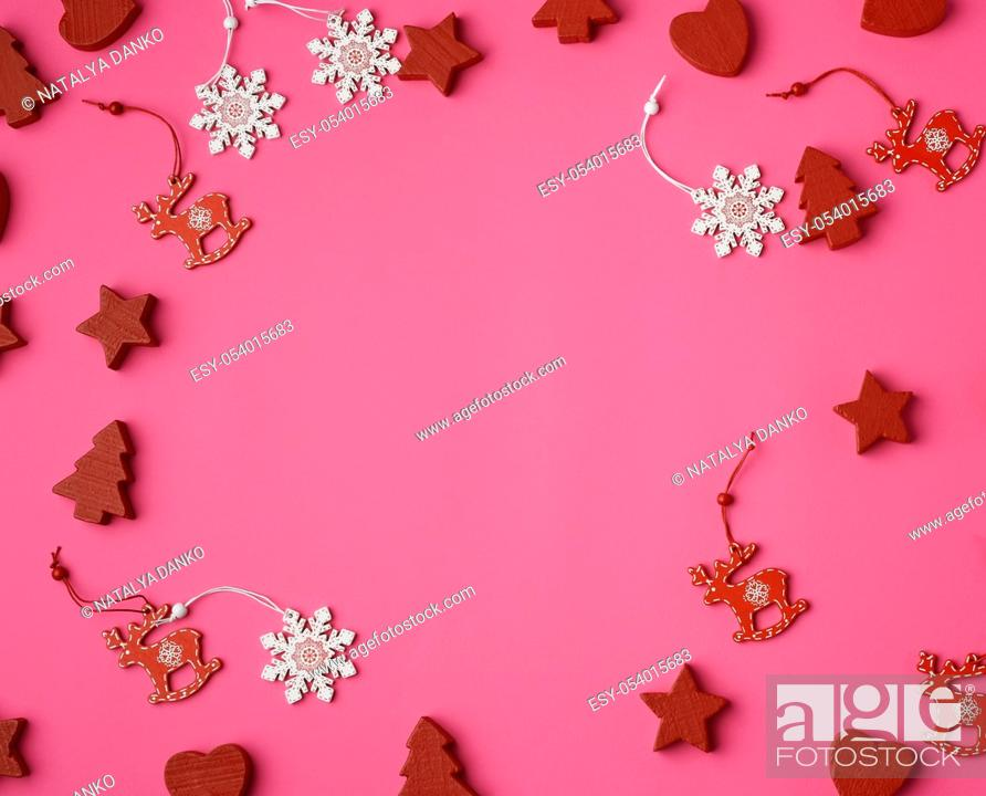 Stock Photo: wooden carved Christmas decorations for the holiday tree on a pink background.