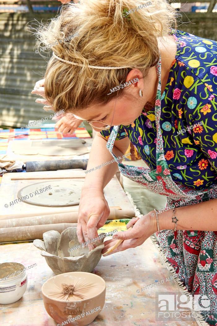 Imagen: Amateur artists while modeling clay to obtain raku ceramics.