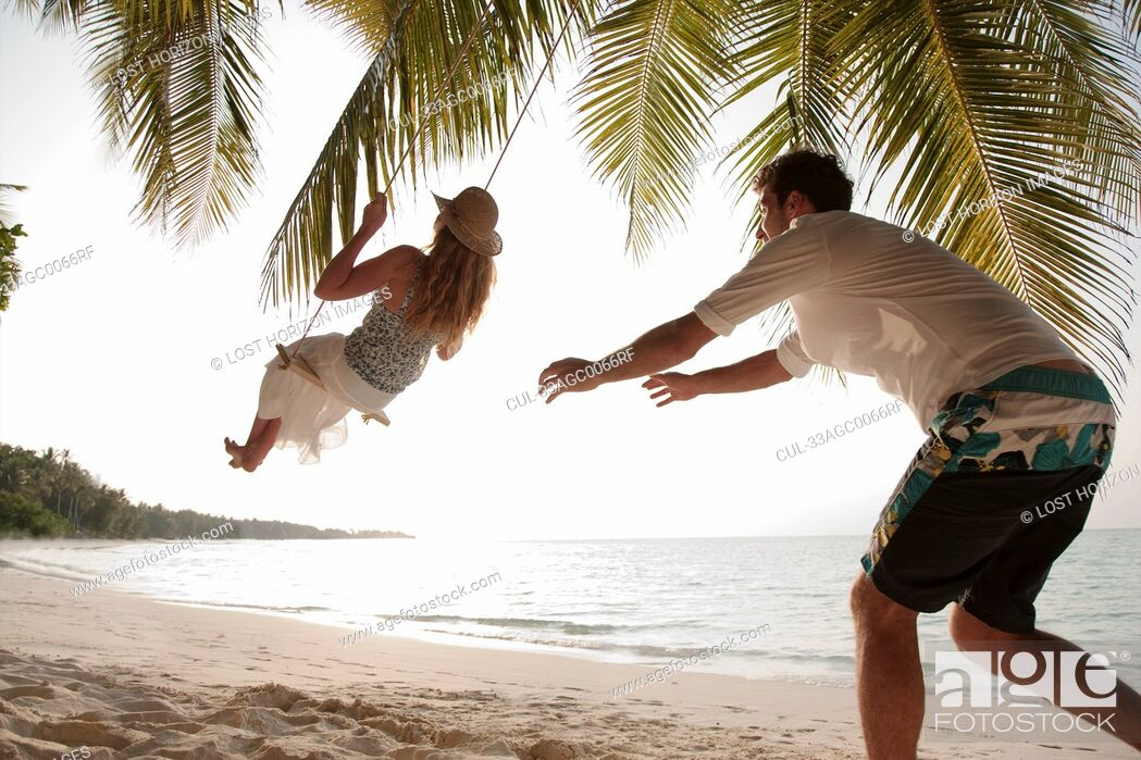 Imagen: Man pushing swinging woman at beach.