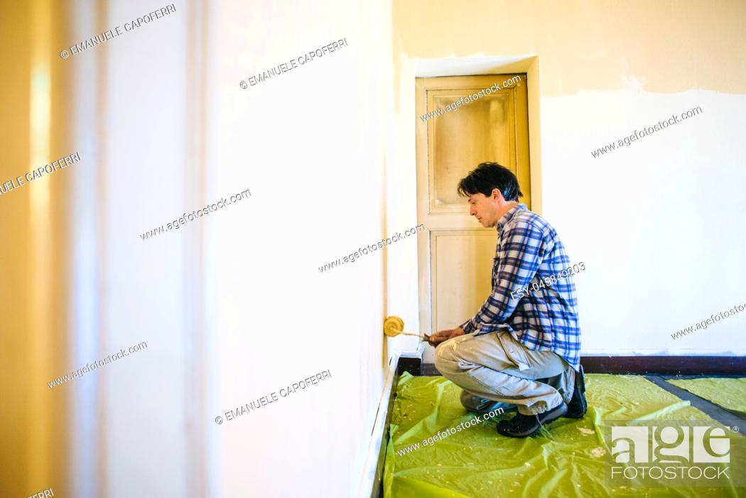 Imagen: husband father of forty years, paints house wall - man painting wall of a room-man performs DIY painting at home.