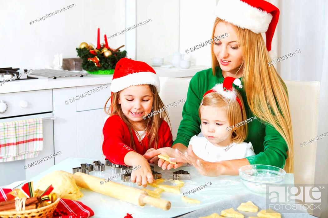 Stock Photo: Two adorable little girls and mother baking Christmas cookies in the kitchen.