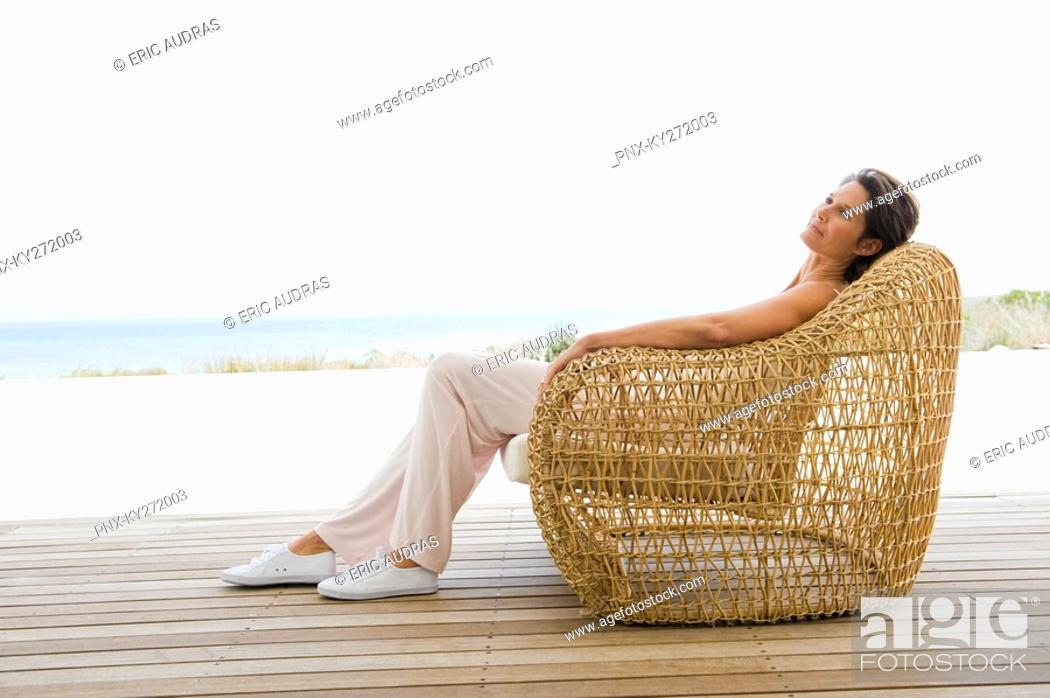 Stock Photo: Woman reclining on a chair on the beach.