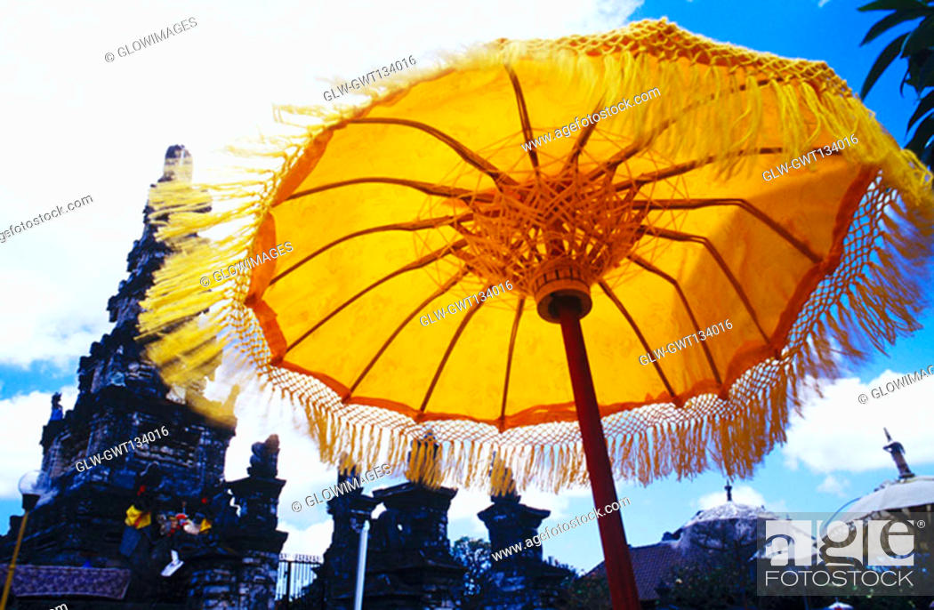 Stock Photo: Low angle view of a sunshade in front of a temple, Bali, Indonesia.