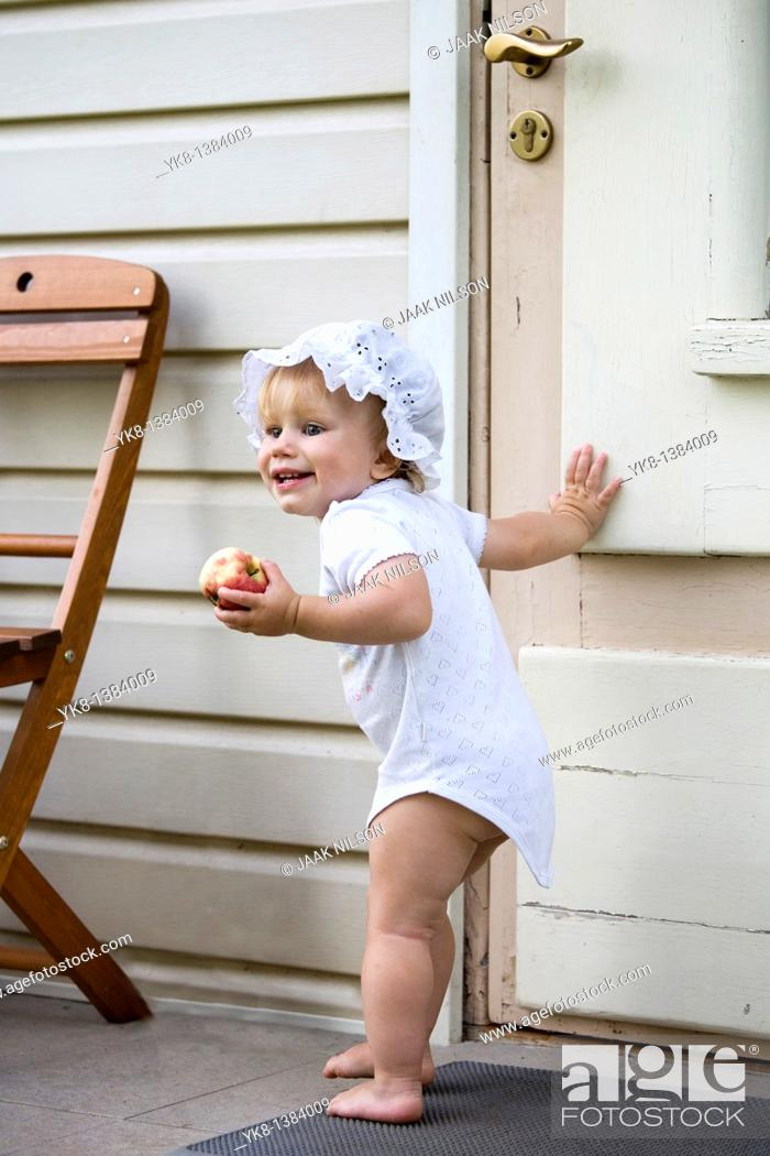 Stock Photo: Happy One Year Old Baby Girl Standing Outside by Wooden Door with Apple in Hand.
