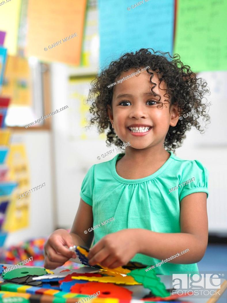 Stock Photo: Girl assembling puzzles in classroom portrait.