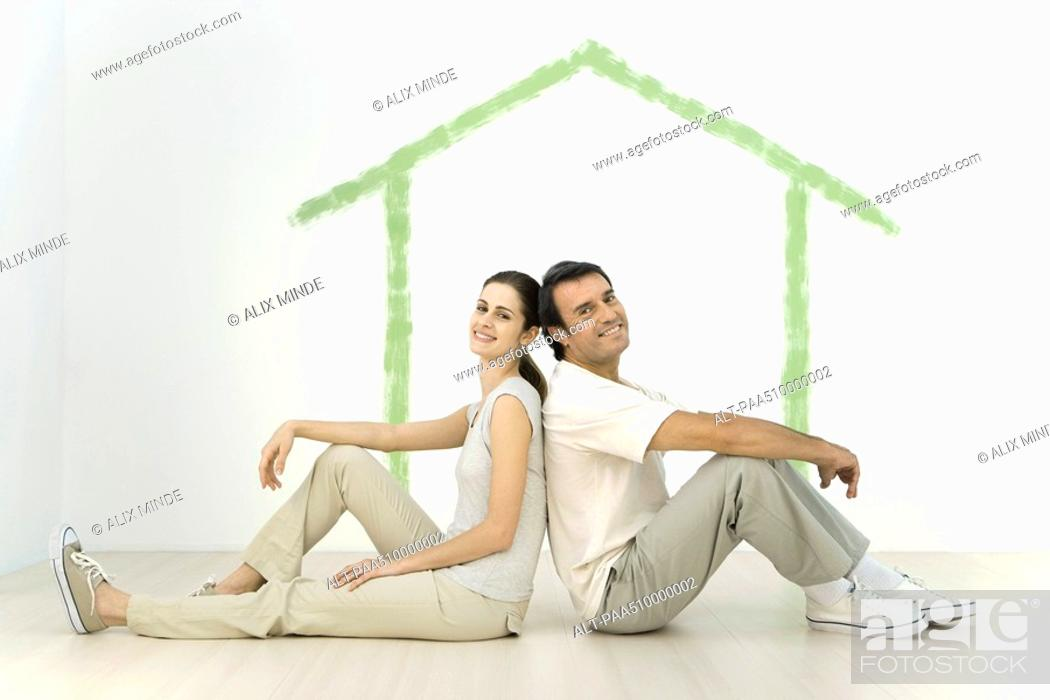 Stock Photo: Couple sitting back to back in front of an outline of a house painted on wall.
