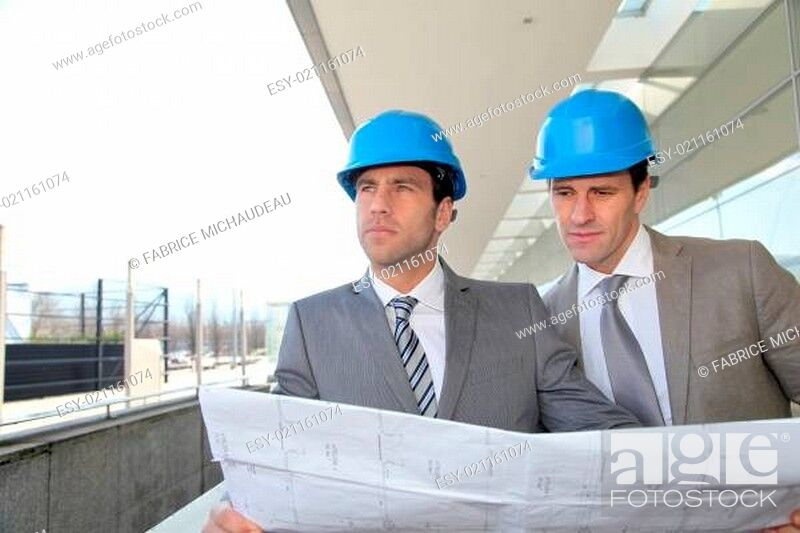 Imagen: Architects checking construction site with plan outside.