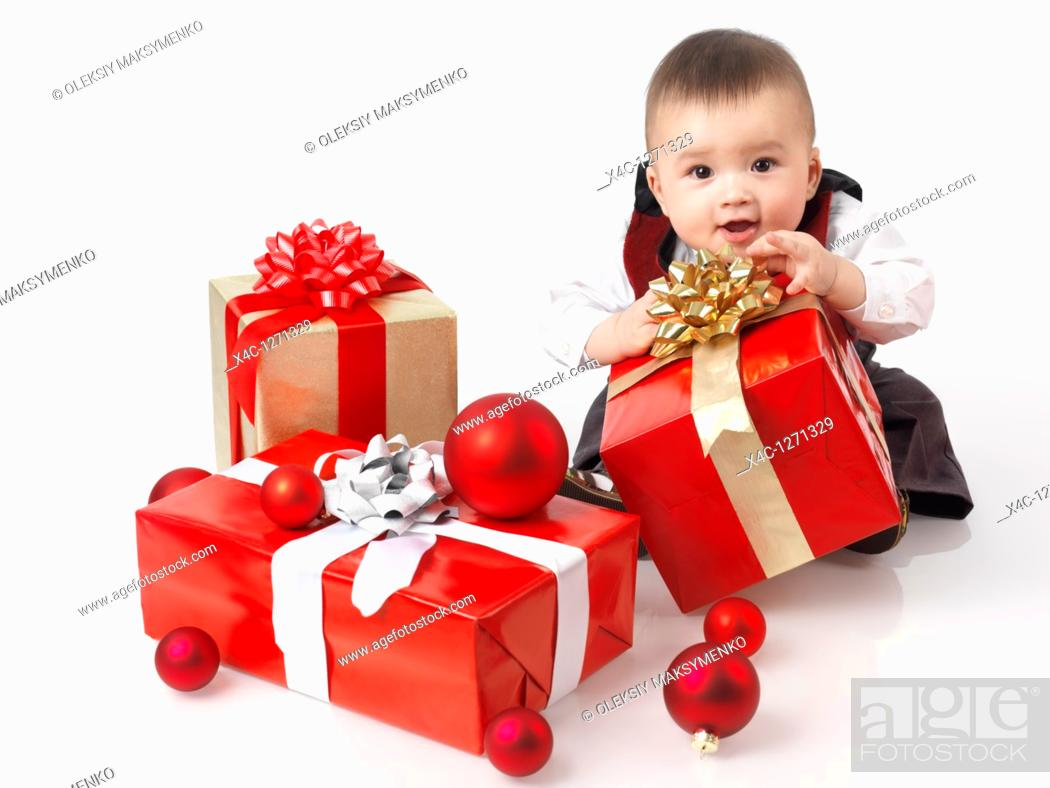 Stock Photo: Happy six month old baby boy opening Christmas presents  Isolated on white background.