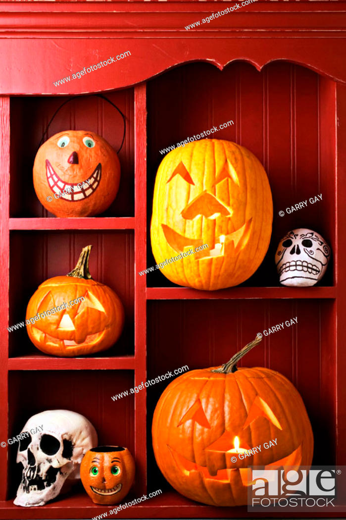 Stock Photo: An old red cabinet with Halloween items, carved pumpkins, skulls.
