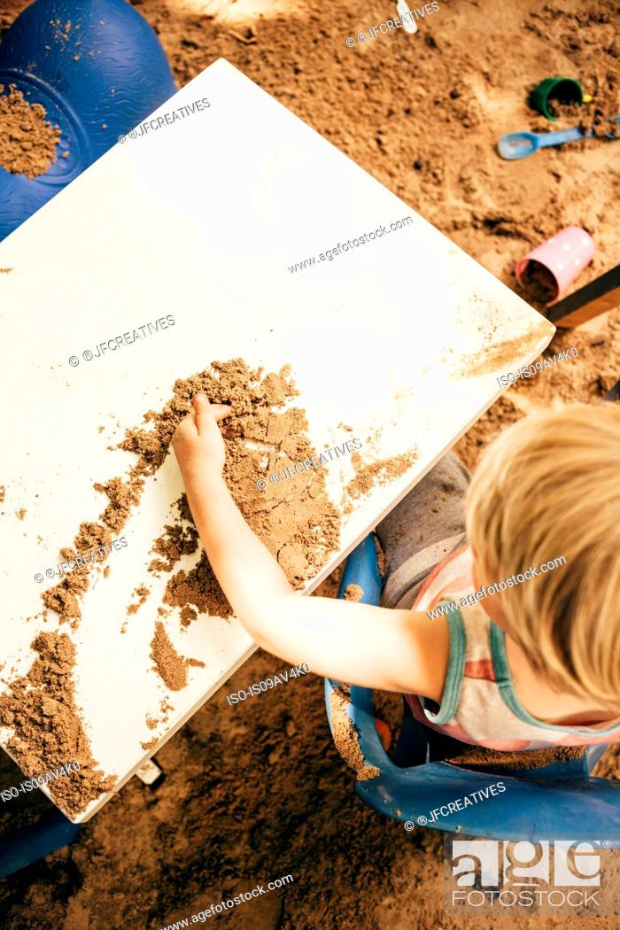 Stock Photo: Overhead view of boy sitting at table in sandpit playing with sand.