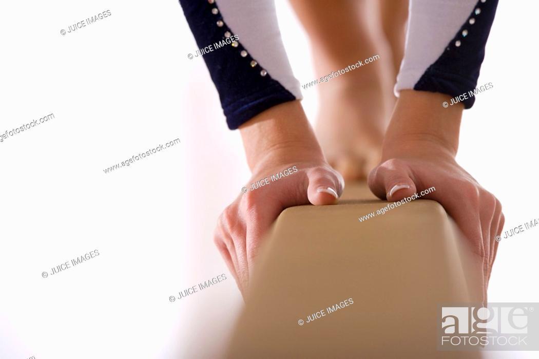 Stock Photo: Female gymnast on balance beam, close-up of hands.