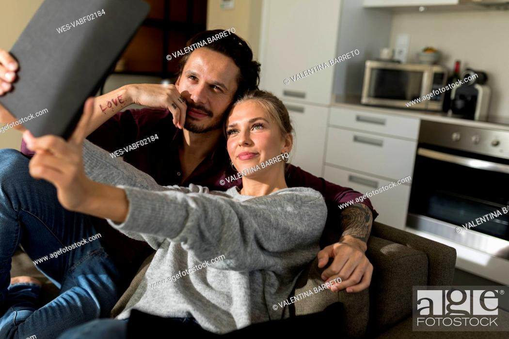 Stock Photo: Couple sitting on couch in livingroom, taking pictures with their digital tablet.