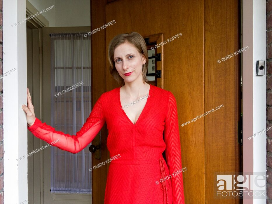 Stock Photo: Tilburg, Netherlands. Portrait young adult woman wearing a red dress standing in an opened domestic front door.